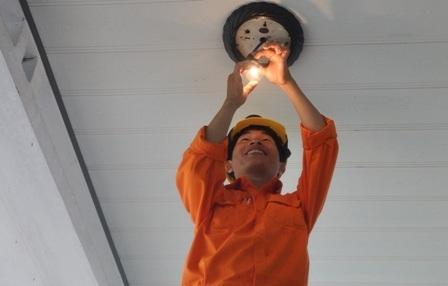Nhân viên Công ty Điện lực Quảng Nam hỗ trợ các gia đình lắp đặt bóng đèn