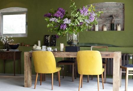 Tường màu xanh lá tương phản với những chiếc ghế vàng và chất liệu gỗ tự nhiên.
