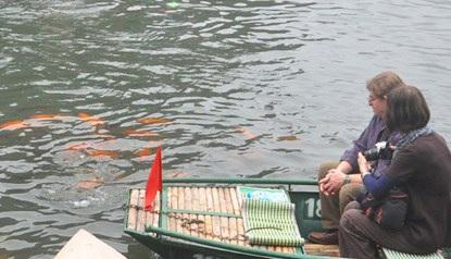 Hai du khách nước ngoài cũng tỏ ra khá bất ngờ, thích thú ngắm cá.