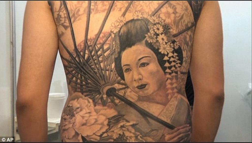 Một người đàn ông với hình xăm phụ nữ Nhật Bản trong trang phục truyền thống trên lưng.