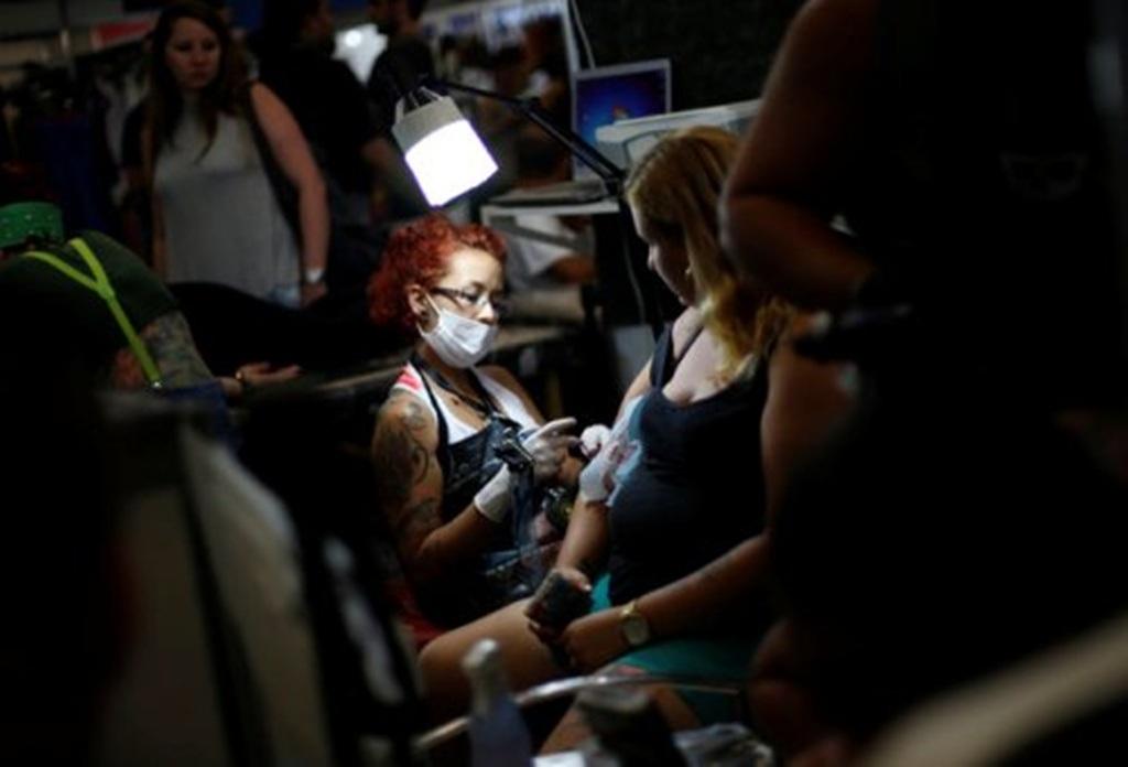 Một nữ nghệ sỹ miệt mài làm việc. Khá nhiều người khác đang ngồi chờ đợi tới lượt.