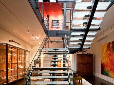 Cầu thang bằng kính làm tăng thêm cảm giác hiện đại cho phòng khách.
