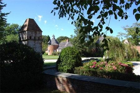 Ngôi nhà chính của dinh thự nằm phía sau những bức tường cổ và và nhiều bụi cây.