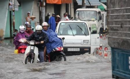 Nhiều người cùng nhau dùng xà beng cạy nắp cống trên đường Phạm Văn Đồng để nước thoát.
