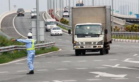 Một chiếc xe chở hàng qua hệ thống cân được biển báo điện tử thông tin quá tải (QT).