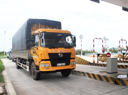 Nhân viên trạm thu phí Long Phước đang hướng dẫn xe tải vào làn để cân tải trọng xe.