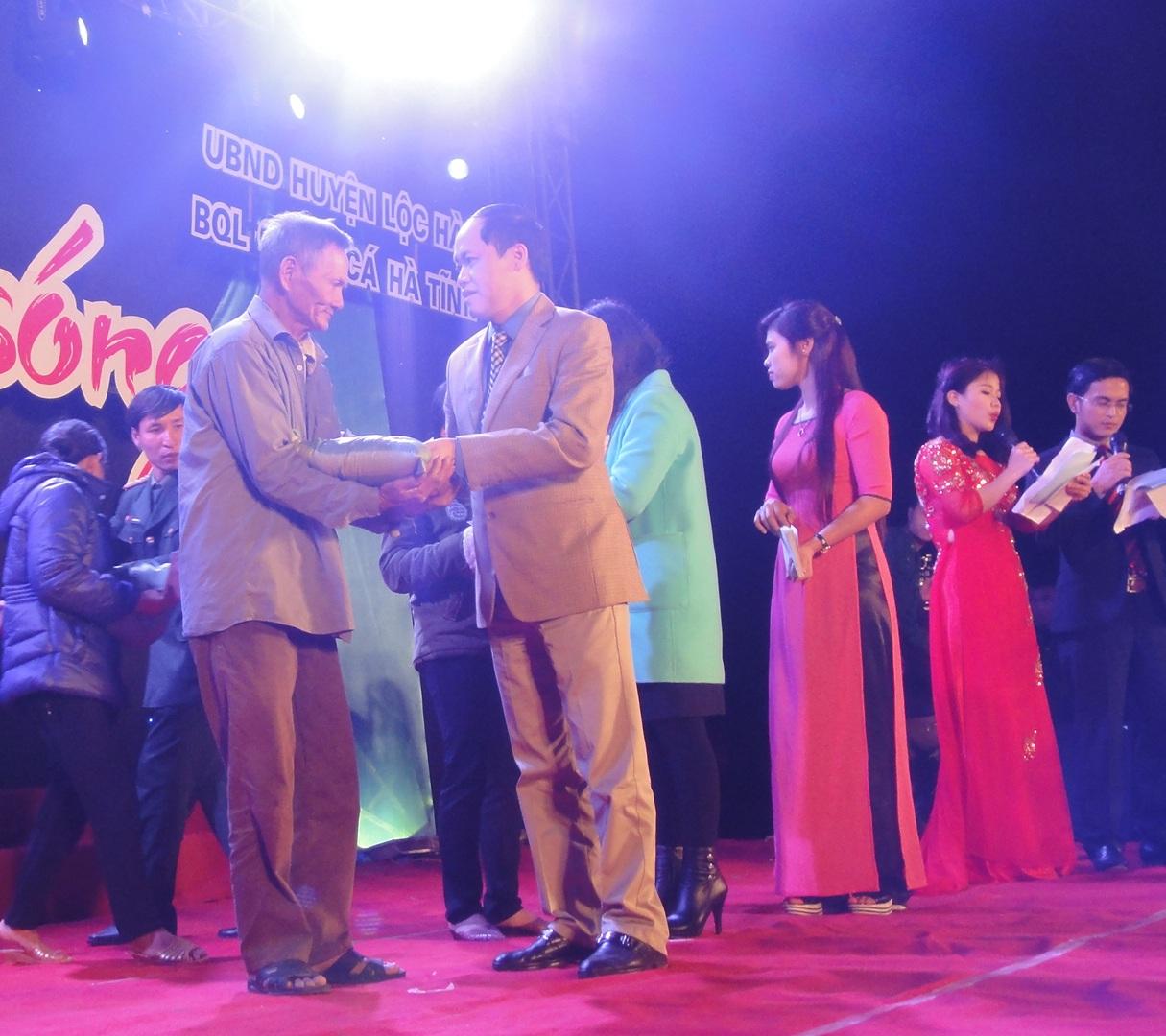 Đồng chí Nguyễn Hồng Lĩnh phó chủ tịch UBND tỉnh trao quà cho các ngư dân.