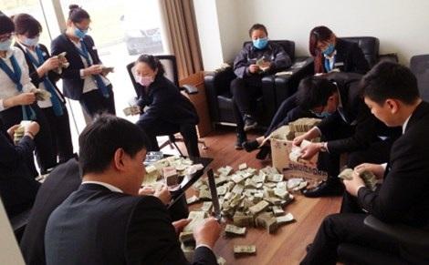 Nhân viên một đại lý xe hơi tại Trung Quốc đếm những tờ 1 Nhân dân tệ