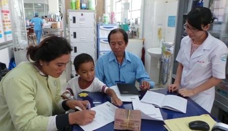 Đại diện bệnh viện Bệnh Nhiệt Đới làm thủ tục trao tiền cho gia đình bé Phát