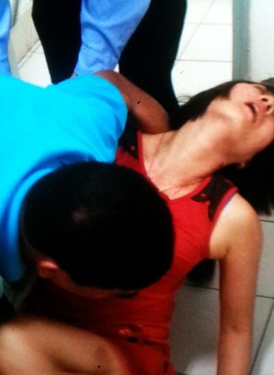 Nữ khách hàng bị đánh ngất xỉu đang được dìu đưa đi cấp cứu (ảnh cắt từ clip)