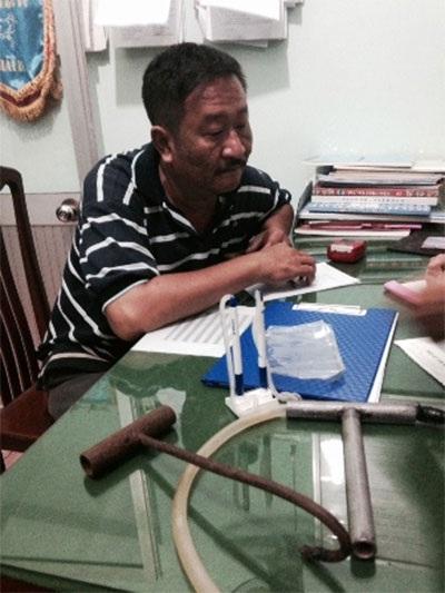Ông Trần Anh Tấn và một số dụng cụ bơm nước vào heo. Ảnh: Minh Sơn