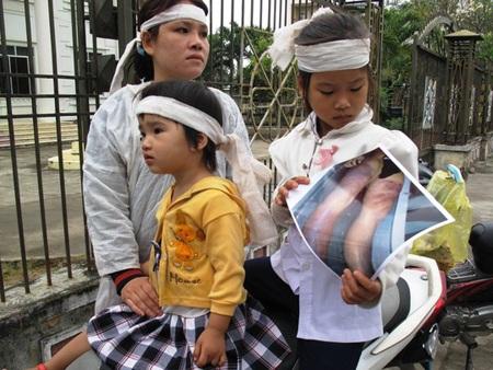 Chị Trần Thị Tâm (vợ Kiều) cùng 2 con mang theo ảnh cồng ra tòa