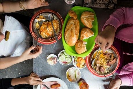 Khách hàng đang thưởng thức những đĩa trứng ốp la ăn kèm với bánh mì trong quán Hòa Mã.