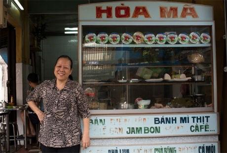 Bà Hạnh tười cười trước quán bánh mì của gia đình mình.