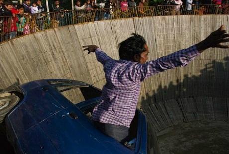 Một nghệ sĩ cùng biểu diễn chào đón người xem một cách liều lĩnh khi vươn mình ra ngoài xe