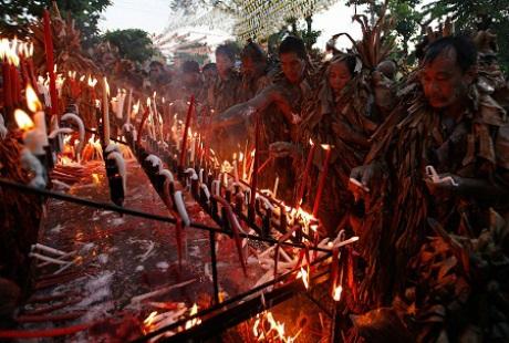 Những người mộ đạo đang thắp nến trong nghi thức tôn giáo địa phương.