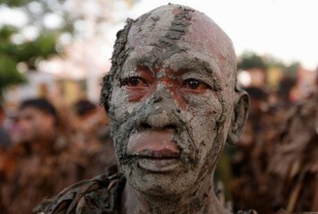 Một người đàn ông toàn thân phủ đầy bùn tham gia lễ hội để cầu bình an và mùa màng bội thu.