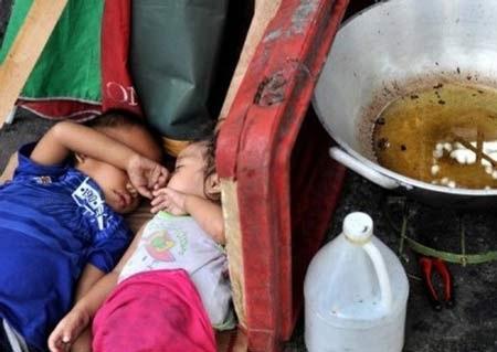 Những đứa trẻ ngủ bên chảo dầu trên một con phố ở thủ đô Manila, Phillippin