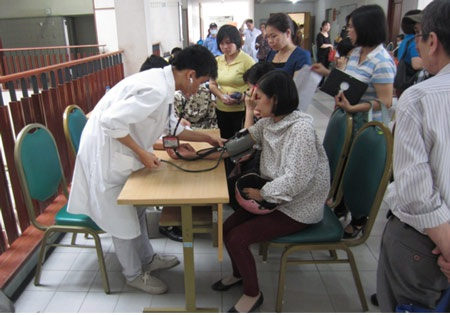 Bệnh nhân được đo huyết áp, cân nặng, chiều cao trước khi vào hội trường để BS khám.