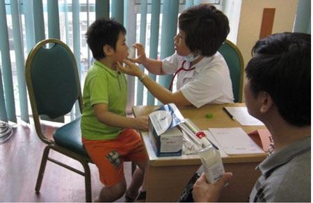 BS hướng dẫn sử dụng thuốc cho bệnh nhân tại 1 bàn khám Nhi, có sự theo dõi của phụ huynh của trẻ
