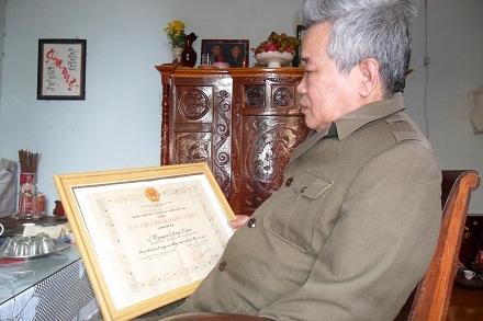 Thương binh Nguyễn Văn Tiến bên tấm Huy chương kháng chiến được Nhà nước khen tặng.