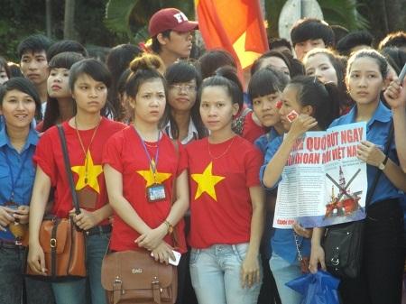 Một nữ sinh với chiếc áo đỏ sao vàng 5 cánh và hình trái tim trênkhuôn mặt.