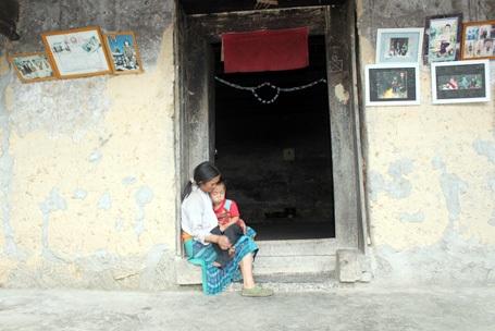 Chị Ly Thị Chúa ôm con bên bậu cửa, hình ảnh quen thuộccủa phụ nữ người Mông