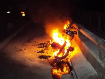 Chiếc xe máy cháy rụi trên cầu Rạch Miễu.