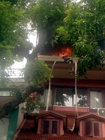 Lính cứu hỏa phải leo ra ban công tầng 3 để dập lửa.
