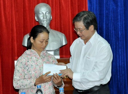 Đại diện Quỹ hỗ trợ ngư dân tỉnh Quảng Ngãi (phải) trao 20 triệu đồng đến chị Lê Thị Mai.