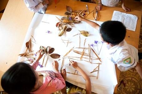 Các em học sinh đang hoàn thiện một bức tranh từ lá cây trong