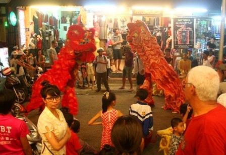 Lân múa kiểu chầu trước cửa hàng bán đồ lưu niệm ở phố Tây đường Phạm Ngũ Lão