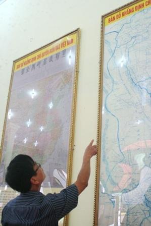 1 người đang chăm chú tìm các quần đảo Hoàng Sa và Trường Sa của Việt Nam trên bản đồ.