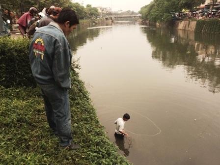 Người dân xuống sông bắt cá.