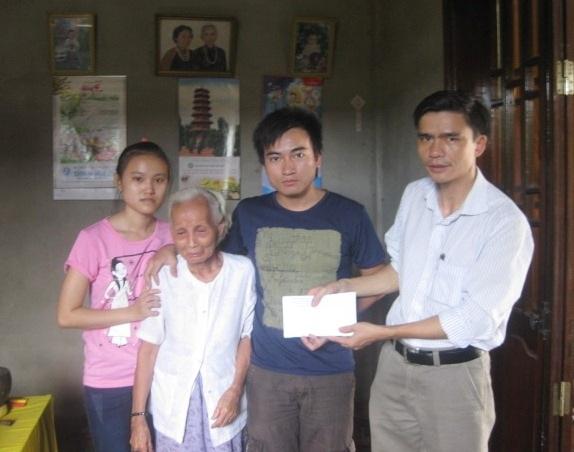 Em Vân (ngoài cùng bên trái) cùng bà ngoại già, anh trai nhận quà từ Hội Chữ thập đỏ.