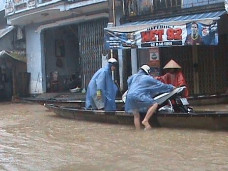Đưa xe máy lên ghe qua vùng nước sâu.