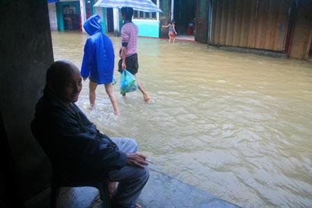 Một cụ ông già gần 80 tuổi ngồi nhìn nước lũ xung quanh phố cổ Bao Vinh