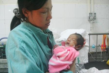 Một cháu nhỏ bị bệnh nặng người nhỏ và rất ốm trong vòng tay mẹ