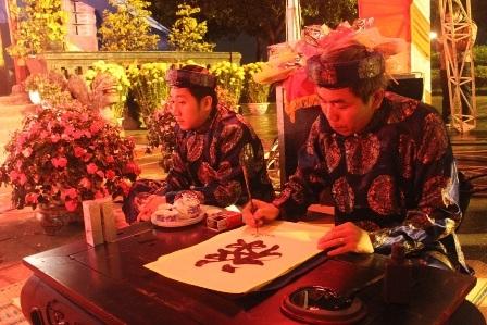 Nhà thơ Hải Trung, Giám đốc Bảo tàng Cổ vật Cung đình Huế (phải) viết chữ thư pháp đẹp tặng khách