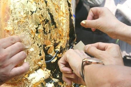 Từng miếng vàng nhỏ được đính vào tượng sơn đen