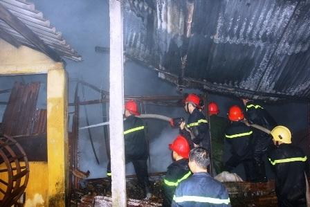 Lính cứu hỏa xông qua mái kho phế liệu bị sập
