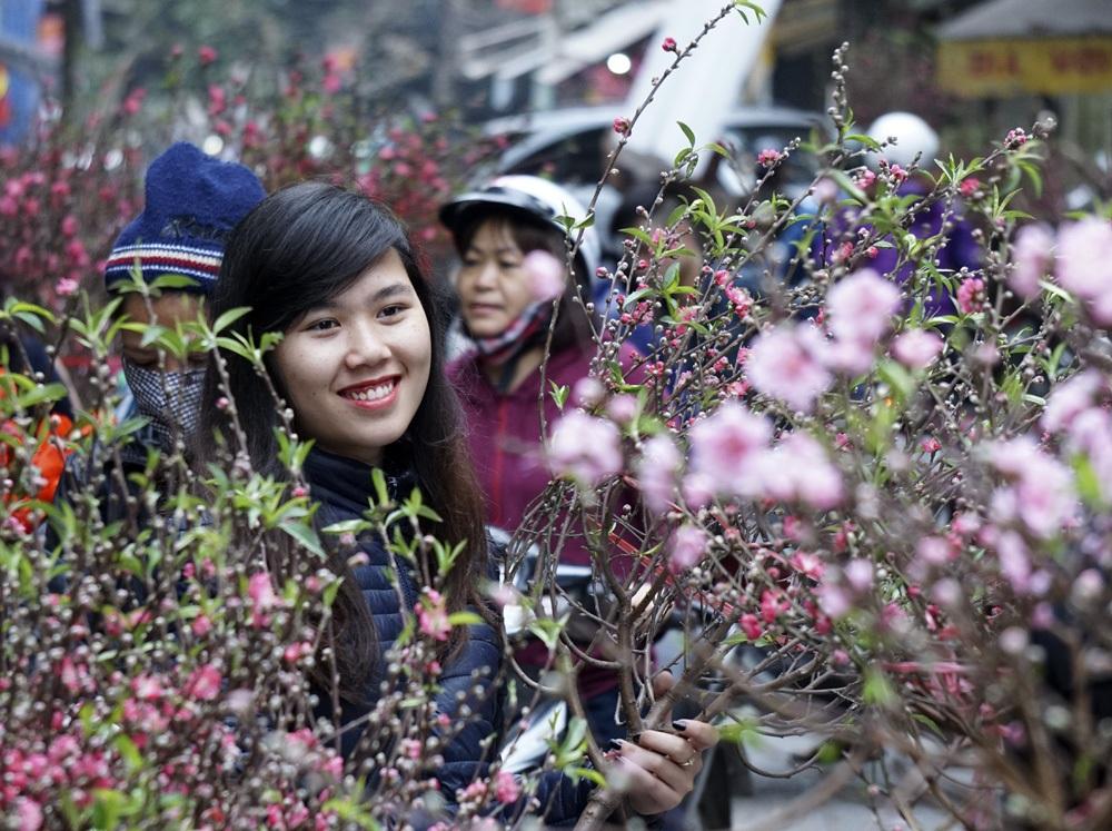 Một cô gái bán hoa đào cùng nụ cười tươi đón khách mua đào sớm.