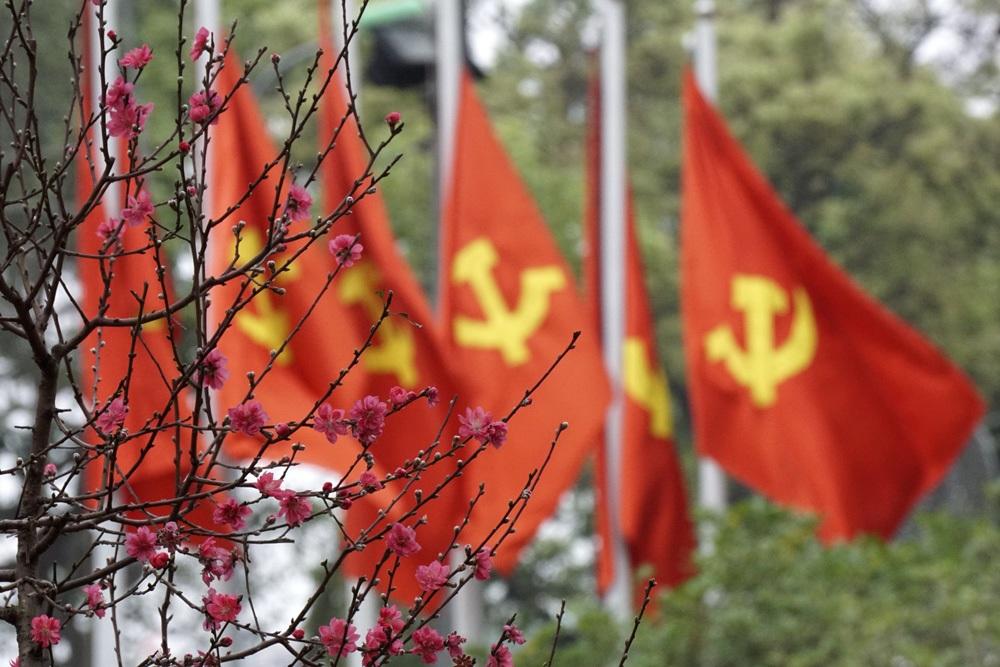Cờ Tổ quốc và cờ Đảng hòa quyện trong sắc đỏ hoa đào trên đường phố Thủ đô.