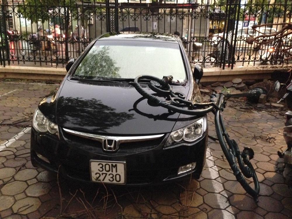 Một cột đèn đỗ liên hoàn theo gốc cây xà cừ đè lên một chiếc ô tô khác.