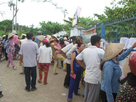 Các phụ huynh đứng ngoài cổng trường xem danh sách, chờ nhận tiền cho con