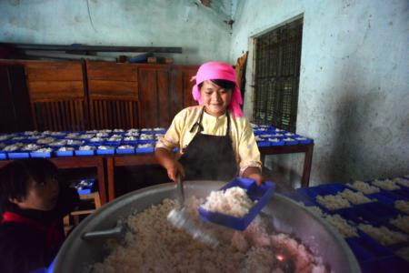 Lầu Thị May đang chia cơm cho học sinh - em là một trong 5 người