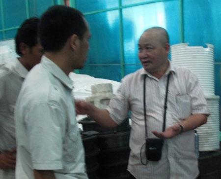 Ông Cường (phải) trao đổi công việc với cán bộ kỹ thuật trong quá trình sản xuất