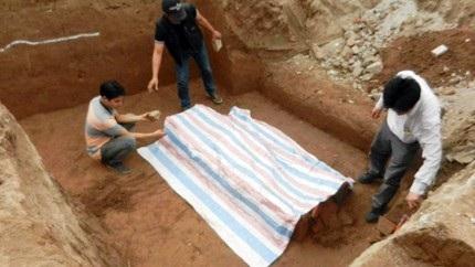 Ngôi mộ cổ vừa phát hiện đang được các nhà khoa học che bạt bảo vệ