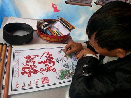 Ông Thành đang vẽ thêm cái đuôi gà để phân biệt giới tính người được nhận chữ