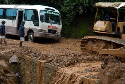 Xe ủi kéo xe khách vượt qua vũng lầy và khu vực sạt lở để giải tỏa ách tắc.